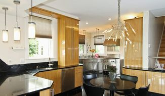 The kitchen features stainless steel appliances and light fixtures that are paired with light cabinetry and black marble flooring.