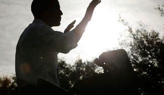 A silhouetted President Obama gestures during a morning campaign event at Ybor City Museum State Park on Thursday in Tampa, Fla. Meanwhile, in Cleveland, another battleground state, Ohio, his campaign is deluging the airwaves with ads. (Associated Press)