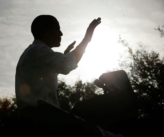 A silhouetted President Obama gestures during a morning campaign event at Ybor City Museum State Park on Thursday in Tampa, Fla. Meanwhile, in Cleve