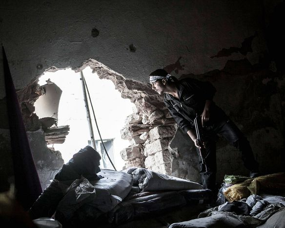 A Free Syrian Army fighter watches over an enemy position Wednesday as rebels belonging to the Liwa Al Tawhid group fight at the Moaskar front line in the Karmal Jabl neighborhood in Aleppo. The protracted Syrian war is spilling into other countries. (Associated Press)