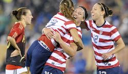 Germany's Verena Faisst, back left, reacts as United States' Tobin Heath, Abby Wambach and Lauren Cheney, left to right, celebrate Heath's goal to put the United States up 2-1 during the second half of a 2-2 tie in an international friendly soccer match in East Hartford, Conn., on Tuesday, Oct. 23, 2012. (AP Photo/Fred Beckham)