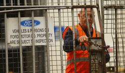 A security guard locks a gate at the Ford Transit Assembly Plant in Southampton, England, after workers were told on Thursday, Oct. 25, 2012, that the plant will close, with the loss of up to 1,500 jobs. (AP Photo/Press Association, Chris Ison)