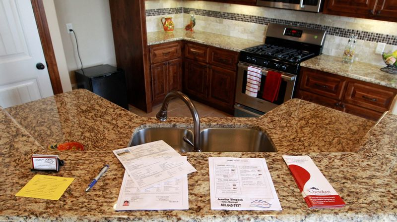 In this Sept. 21, 2012, photo, fliers are stacked on the granite counter of a new home for sale in Oklahoma City. U.S. sales of new homes jumped in September to the highest level in more than two years, further evidence of a sustained housing recovery that could help lift the lackluster economy. The Commerce Department said on Wednesday, Oct. 24, 2012, that new-home sales rose 5.7 percent in September to a seasonally adjusted annual rate of 389,000. That's up from a rate of 368,000 in August and the highest rate since April 2010, when a federal homebuyer tax credit inflated sales. (AP Photo/Sue Ogrocki)