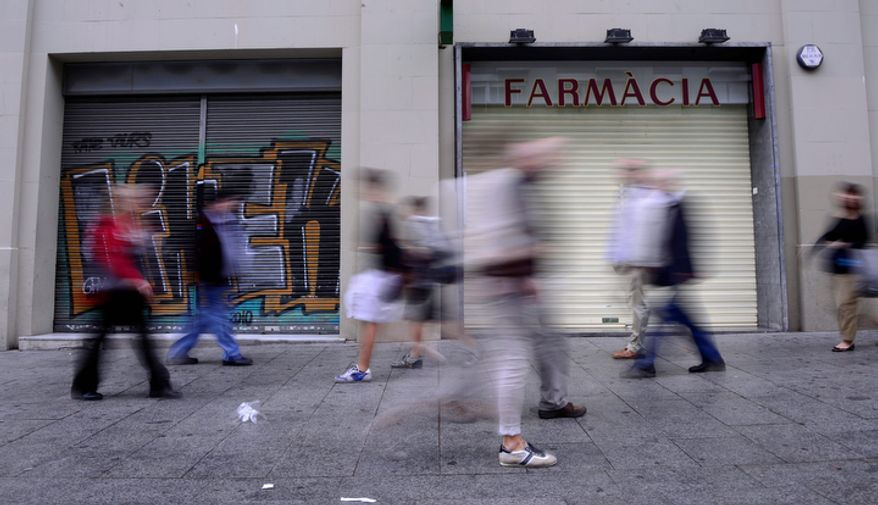 Pedestrians pass in front a closed pharmacy in Barcelona on Thursday, Oct. 25, 2012. Pharmacies in Catalonia on Thursday staged a strike to protest delays in government payments of 190 million euros ($246.30 million) for drugs they dispensed in July and August. (AP Photo/Manu Fernandez)