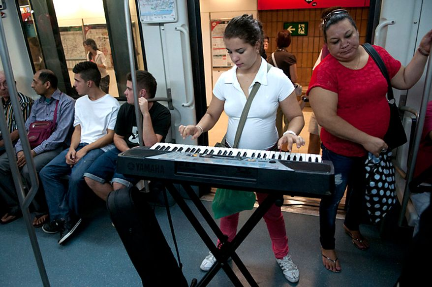 A young woman plays music on her portable keyboard for tips on a subway train in downtown Barcelona on Saturday, Sept. 22, 2012. (Rod Lamkey Jr./The Washington Times)