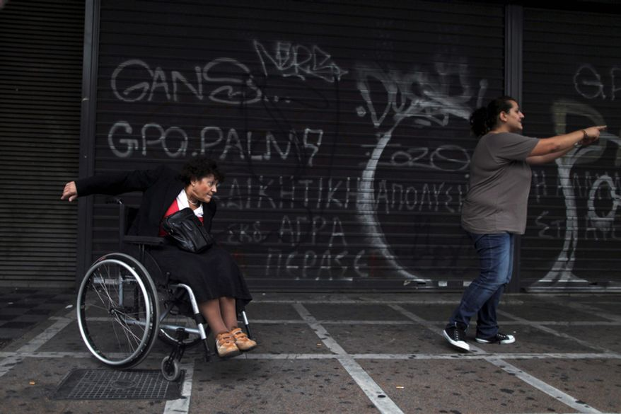 A woman with disabilities takes part in a march against the Greek government's new austerity measures outside the Labor Ministry in central Athens on Tuesday, Oct. 23, 2012. Greece is negotiating with its creditors on a new austerity program for the next two years. Until an agreement is struck, Athens will not receive a desperately needed new loan originally scheduled for June. Without it, the government will run out of money on Nov. 16. (AP Photo/Petros Giannakouris)