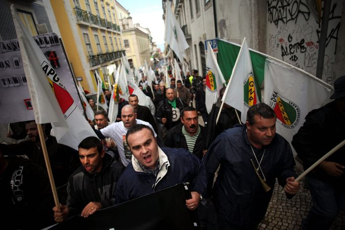Demonstrators shout slogans during a protest called by a Portuguese Republican Guard force association against economic austerity measures by Portugal's government in Lisbon on Wednesday, Oct. 24, 2012. Portugal's center-right coalition government announced a state budget for 2013 that, if approved, it will mean a significant tax increase and cuts in social services and civil service layoffs. (AP Photo/Francisco Seco)
