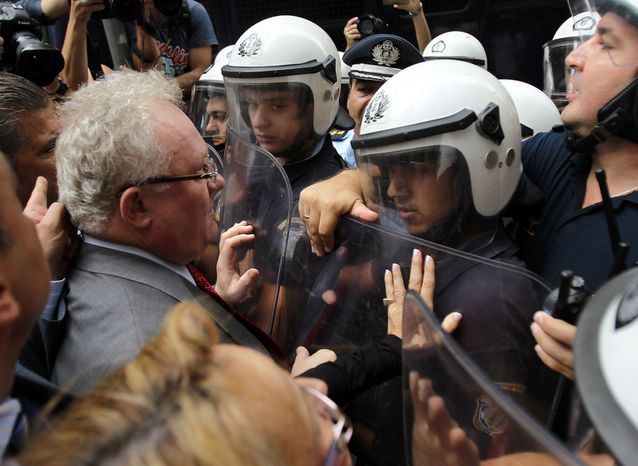 Lawyers and doctors scuffle with riot police during an anti-austerity protest outside the Finance Ministry in Athens on Wednesday, Oct. 17, 2012. Civil servants and private sector workers staged a nationwide general strike on Thursday to protest new austerity measures the government is still negotiating with the debt-ridden country's international creditors. (AP Photo/Thanassis Stavrakis)