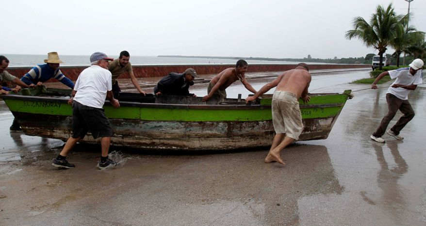 People remove a boat from the water ahead of the arrival of Hurricane Sandy in Manzanillo, Cuba, Wednesday, Oct. 24, 2012. Hurricane Sandy pounded Jamaica with heavy rain as it headed for landfall near the country's most populous city on a track that would carry it across the Caribbean island to Cuba, and a possible threat to Florida. (AP Photo/Franklin Reyes)