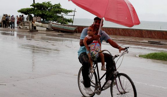 A man balances a child and umbrella on his bike as it rains during the approach of Hurricane Sandy in Manzanillo, Cuba, Wednesday, Oct. 24, 2012. Hurricane Sandy pounded Jamaica with heavy rain as it headed for landfall near the country's most populous city on a track that would carry it across the Caribbean island to Cuba, and a possible threat to Florida. (AP Photo/Franklin Reyes)