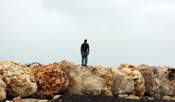 A man stands on boulders placed as a barrier to help prevent flooding of the seaside road that leads to the international airport as Hurricane Sandy approaches Kingston, Jamaica, Wednesday, Oct. 24, 2012. Hurricane Sandy pounded Jamaica with heavy rain as it headed for landfall near the country's most populous city on a track that would carry it across the Caribbean island to Cuba, and a possible threat to Florida. (AP Photo/Collin Reid)