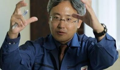 ** FILE ** In this Oct. 22, 2012 photo, Yuichi Okamura, manager of the Water Treatment System Department at the Fukushima Dai-ichi nuclear power plant, gestures while speaking during an exclusive interview at the Tokyo Electric Power Co. (TEPCO) headquarters in Tokyo. (AP Photo/Shizuo Kambayashi)