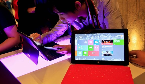 In this Tuesday Oct. 23, 2012, file photo, a Chinese man tries out the new Surface tablet computer made by Microsoft at a show in Shanghai ahead of the launch of the operating system on Oct. 26. With the release of Windows 8, PC makers are doing their best to blur the boundaries between the PC and tablet with an array of devices that mash keyboards and touch screens together in different ways. (AP Photo)