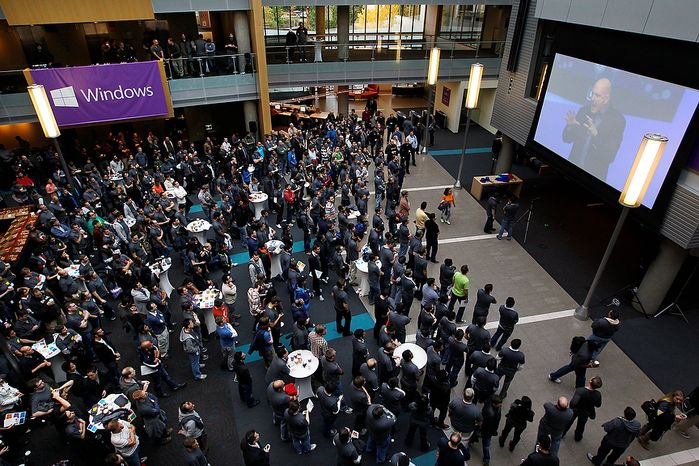 Employees look on as Microsoft CEO Steve Ballmer speaks via a webcast during an event unveiling a new Microsoft Windows operating system Thursday, Oct. 25, 2012, at the company's headquarters in Redmond, Wash.  Designed to run on both PCs and tablet computers, Windows 8 heralds the biggest change to the industry's dominant operating system in at least 17 years. Windows 8 attempts to bridge the gap between personal computers and fast-growing tablets with its touch-enabled interface. The launch event came amid a slew of other tablet offerings ahead of the holidays.  (AP Photo/Elaine Thompson)
