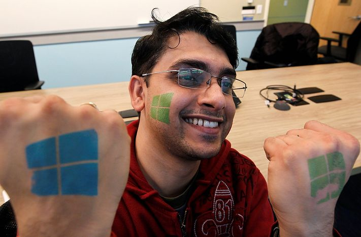 Microsoft engineer Rajas Patil smiles as he displays for the photographer temporary tattoos with the company's logo during an event unveiling a new Microsoft Windows operating system Thursday, Oct. 25, 2012, at the company's headquarters in Redmond, Wash. Though Windows 8 will be backed by a $1 billion marketing campaign, questions surround the software. The biggest one of all: Is it innovative and elegant enough to lure consumers who've fallen in love with an assortment of smartphones, tablet computers and other gadgets? (AP Photo/Elaine Thompson)