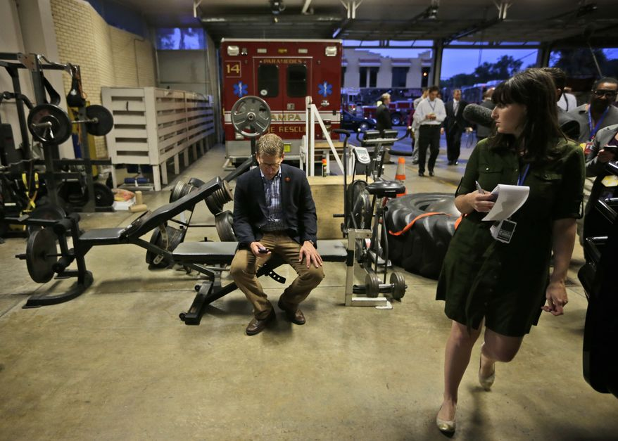 Tampa Bay Times reporter Katie Sanders (right) looks over toward White House spokesman Jay Carney (center), who takes a seat Oct. 25, 2012, in the workout area of Fire House No. 14. in Tampa, Fla., during President Obama's unannounced visit to meet with firefighters. Obama traveled to Florida for a campaign event nearby. (Associated Press)