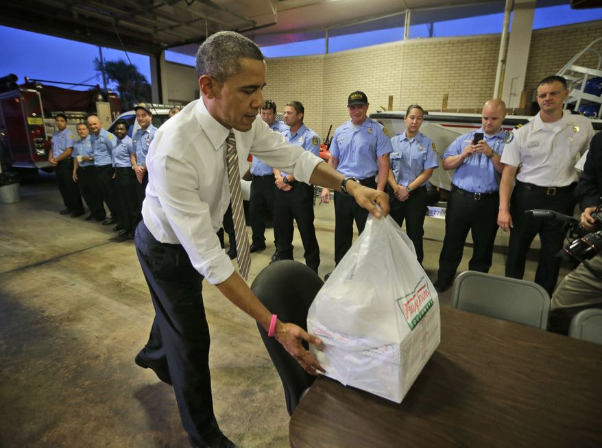President Obama delivers boxes of Krispy Kreme doughnuts that he purchased nearby to firefighters at Fire Station No. 14. in Tampa, Fla., during an unannounced visit on Oct. 25, 2012. (Associated Press)