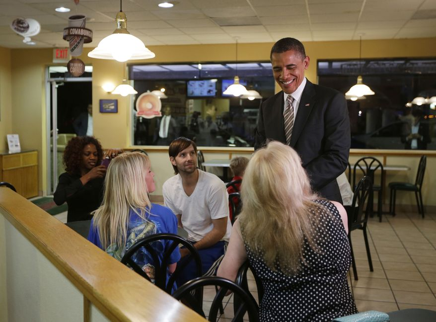 President Obama greets local patrons Oct. 25, 2012, during an unannounced visit to a Krispy Kreme Doughnuts shop in Tampa, Fla. Obama, who traveled to Florida for a campaign event nearby, surprised local patrons when he drove up in the morning. (Associated Press)