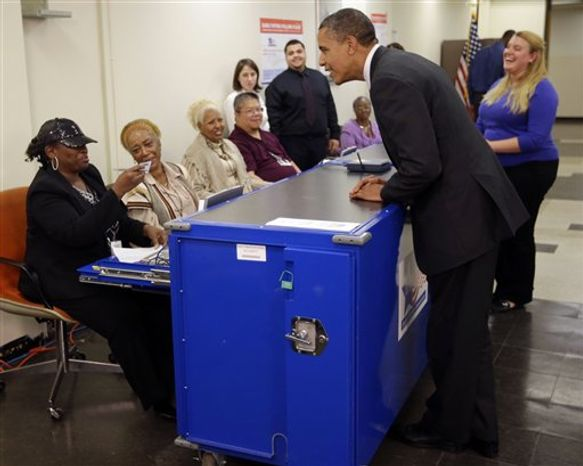 Election official Marie Holmes, left, looks over President Obama's drivers license so he can cast his vote during early voting in the 2012 election at the Martin Luther King Community Center, Thursday, Oct. 25, 2012, in Chicago. (AP Photo/Pablo Martinez Monsivais)