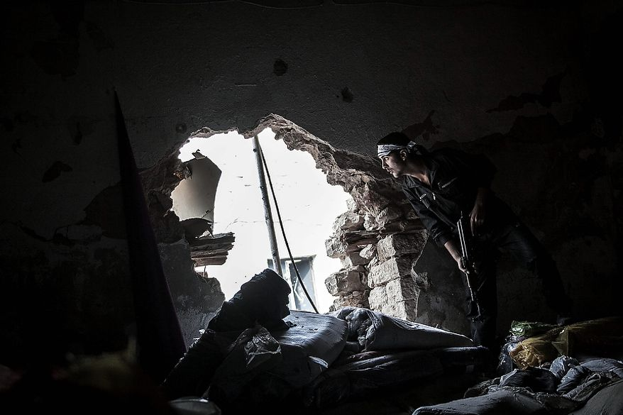 In this Wednesday, Oct. 24, 2012 photo, a Free Syrian Army fighter watches over an enemy position as rebel fighters belonging to the Liwa Al Tawhid group carry out a military operation at the Moaskar front line, one of the battlefields in the Karmal Jabl neighborhood, in Aleppo, Syria. (AP Photo/Narciso Contreras).