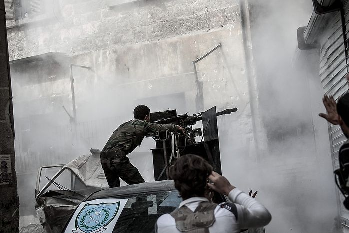 In this Wednesday, Oct. 24, 2012 photo, a Free Syrian Army fighter shoots a gun as rebel fighters belonging to the Liwa Al Tawhid group carry out a military operation at the Karmal Jabl front line, in Aleppo, Syria. (AP Photo/Narciso Contreras).