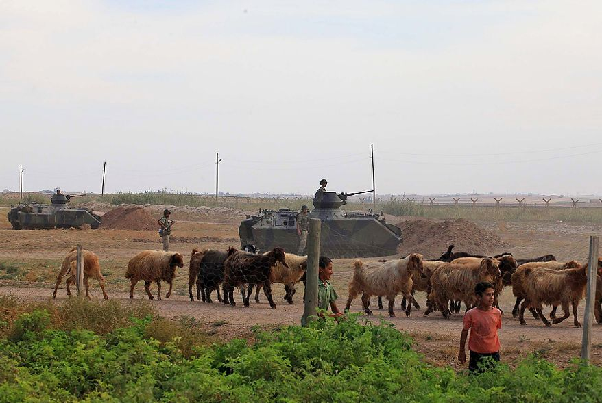 A youth and goats pass by Turkish military stationed on the Turkish side of the border near Syrian rebel-controlled town of Tel Abyad, in Akcakale, Turkey, Friday, Oct. 5, 2012. Turkey's state-run news agency says Turkish troops have returned fire after a mortar shell from Syria again landed on its territory. Turkish artillery has fired at Syrian targets for two straight days after shelling from Syria killed five civilians in Turkey. .(AP Photo)