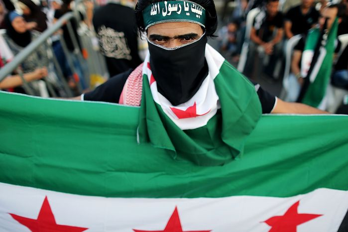 """A Free Syrian Army supporter holds and covers his face with a the Syrian revolutionary flag during an anti-Syrian regime and Salafist group leader Sheikh Ahmad al-Assir demonstration in downtown of Beirut, Lebanon, Sunday, Oct. 14, 2012. Assir, a strong critic of Hezbollah leader Hasan Nasrallah and Syrian President Bashar Assad, has organized multiple protests over the past year in a bid to increase support for the Syrian uprising and mount an offensive against Nasrallah for openly supporting Assadís regime. Arabic writing on his headband reads, """"at your service God's Prophet."""" (AP Photo/Hassan Ammar)"""