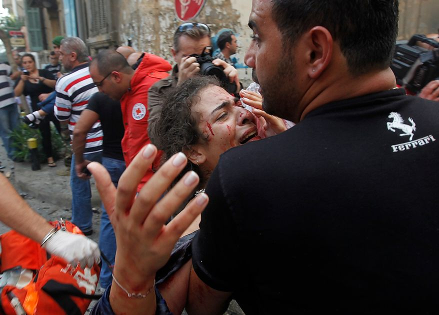 A injured woman is carried by a civilian at the scene of an explosion in the mostly Christian neighborhood of Achrafiyeh, Beirut, Lebanon, Friday Oct. 19, 2012. Lebanese Red Cross and security officials say a car bomb in east Beirut has killed at least eight people and wounded dozens in the worst blast the city has seen in years, coming at a time when Lebanon has seen a rise in tension and eruptions of clashes stemming from the civil war in neighboring Syria. (AP Photo/Hussein Malla)