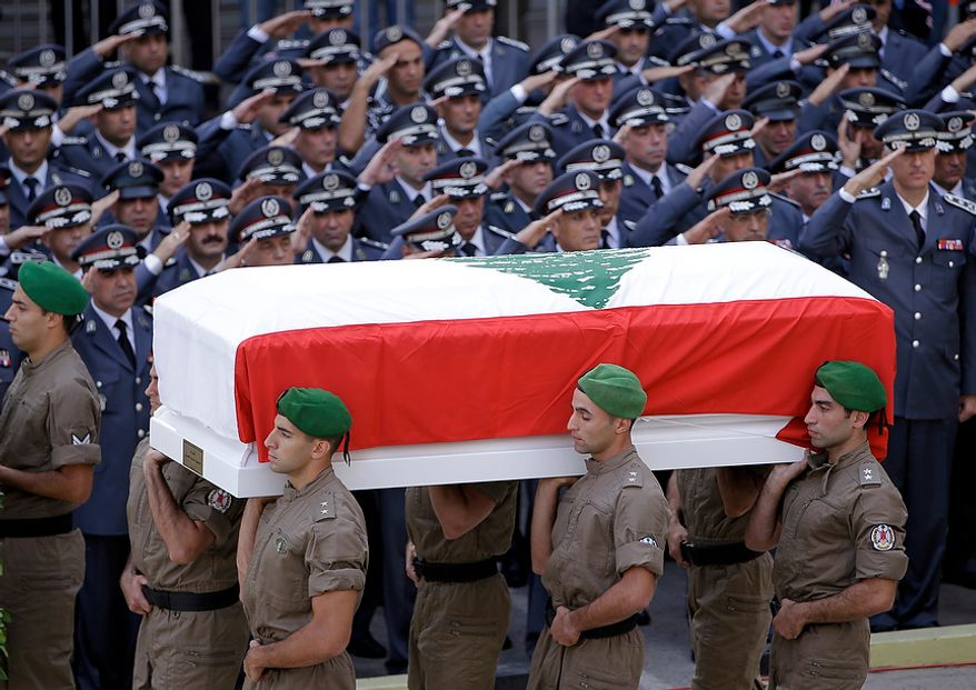 Members of Lebanese police intelligence division units, carry the coffin wrapped by Lebanese flag of Brig. Gen. Wissam al-Hassan who was assassinated on Friday by a car bomb, as police officers salute during his funeral procession at the Lebanese police headquarters in Beirut, Lebanon, Sunday Oct. 21, 2012. Thousands of Lebanese waving the national flag packed a central square in downtown Beirut Sunday for the funeral of a top intelligence official assassinated in a car bombing that many blame on the regime in neighboring Syria. (AP Photo/Hussein Malla)