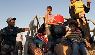Newly arrived Syrian refugees unload their belongings after crossing the border from Tal Shehab, Syria, through the Al Yarmouk River Valley, and arriving near Ramtha, Jordan, on Saturday, Sept. 15, 2012. (AP Photo/Raad Adayleh)