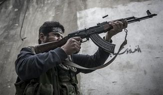 In this Wednesday, Oct. 24, 2012, photo. An Free Syrian Army fighter shoots his gun toward government troops as rebel fighters belonging to the Liwa Al Tawhid group carry out a military operation at the Moaskar front line, one of the battlefields in Karmal Jabl neighborhood, in Aleppo, Syria. (AP Photo/Narciso Contreras).