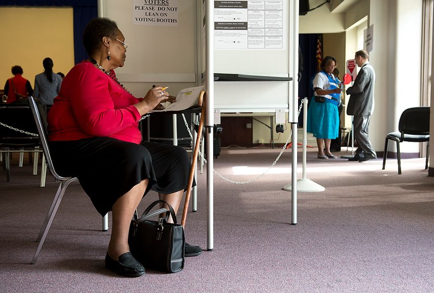 A woman (at left) looks through the paper ballot while voter assistant Sheila Washington (right) hands a number to another voter walking in the door to vote early at Judiciary Square in Washington on Wednesday, Oct. 24, 2012. According to site officials, some 2,400 people have voted here since Monday, when the voting opened. The District of Columbia will open seven more early-voting sites on Saturday (one in each ward), which will be open daily except Sundays until Nov. 3 from 8:30 a.m. to 7 p.m. (Barbara L. Salisbury/The Washington Times)