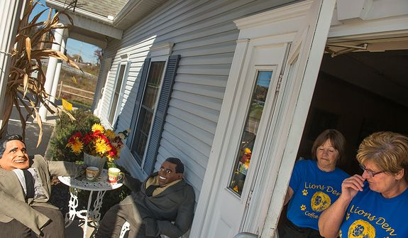 Linda Lee, right, the owner of the Lions Den Coffee Bar, has arranged straw men of President Barack Obama and Gov. Mitt Romney having coffee together outside the front entrance, Fisherville, Pa., Monday, October 22, 2012. Also pictured is Nancy Jacobson, second from right. (Andrew Harnik/The Washington Times)