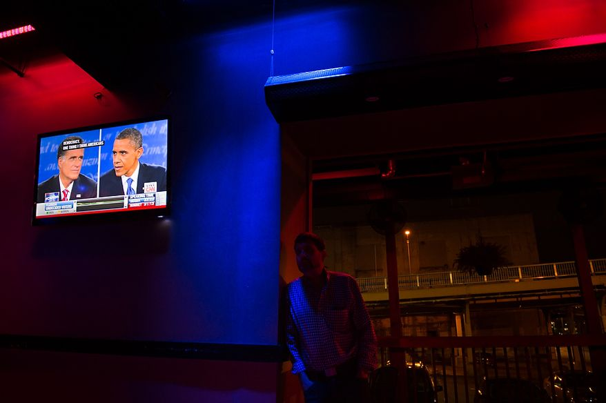 Obama supporter Jim France of Scott Township, Pa., center, watches the third presidential debate at a debate viewing party at Cruze Bar in downtown Pittsburgh, Pa., Monday, October 22, 2012. (Andrew Harnik/The Washington Times)