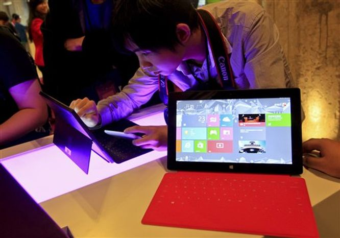 ** FILE ** In this Tuesday, Oct. 23, 2012, file photo, a Chinese man tries out the new Surface tablet computer made by Microsoft at a show in Shanghai ahead of the launch of the operating system. With the release of Windows 8, PC makers are doing their best to blur the boundaries between the PC and tablet with an array of devices that mash keyboards and touch screens together in