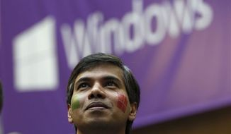 Microsoft program manager Joseph Morris, sporting a pair of company temporary-tattoo logos on his face, looks on during an event unveiling a new Microsoft Windows operating system Thursday, Oct. 25, 2012, at the company's headquarters in Redmond, Wash. (AP Photo/Elaine Thompson)