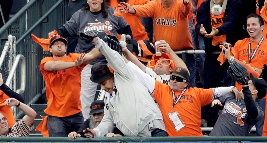 Fans try and catch a home run hit by San Francisco Giants 3B Pablo Sandoval in the first inning of Game 1 of the World Series between the Giants and Detroit Tigers in San Francisco on Oct. 24, 2012. (Associated Press)