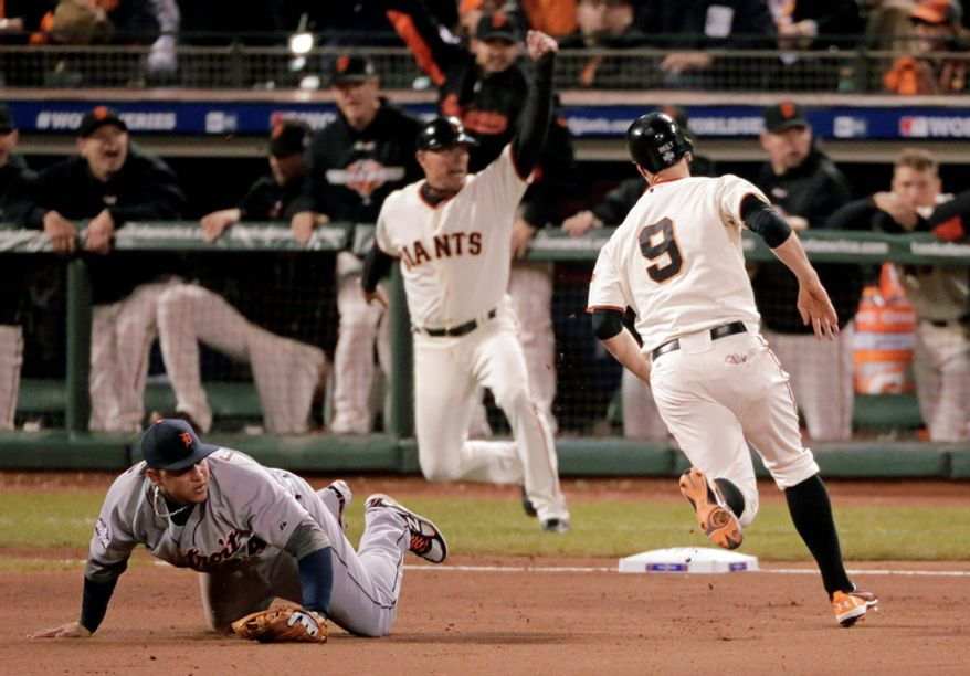 San Francisco Giants 1B Brandon Belt rounds third and heads for home on an RBI single by Barry Zito in the fourth inning as Detroit Tigers 3B Miguel Cabrera falls to the dirt during Game 1 of the World Series in San Francisco on Oct. 24, 2012. (Associated Press)