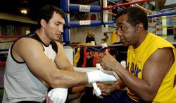 FILE- This Sept. 9, 2004 file photo shows former WBO heavyweight champion Wladimir Klitschko getting his hands taped by trainer Emanuel Steward before a workout at the La Brea Boxing Academy in Los Angeles. Steward, the owner of the legendary Kronk Gym and one of boxing's greatest trainers, has died. He was 68. Victoria Kirton, Steward's executive assistant, says Steward died Thursday Oct. 25, 2012 in a Chicago hospital. She did not disclose the cause of death. (AP Photo/Reed Saxon,File)