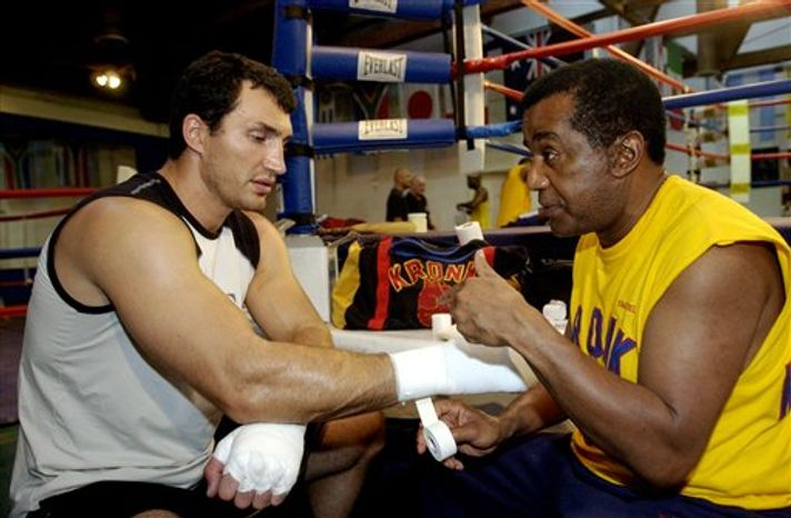 FILE- This Sept. 9, 2004 file photo shows former WBO heavyweight champion Wladimir Klitschko getting his hands taped by trainer Emanuel Steward before a workout at the La Brea Boxing Academy in Los Angeles. Steward, the owner of the legendary Kronk Gym and one of boxing's greatest trainers, has died. He was 68. Victoria Kirton, Steward's executive assistant, says S