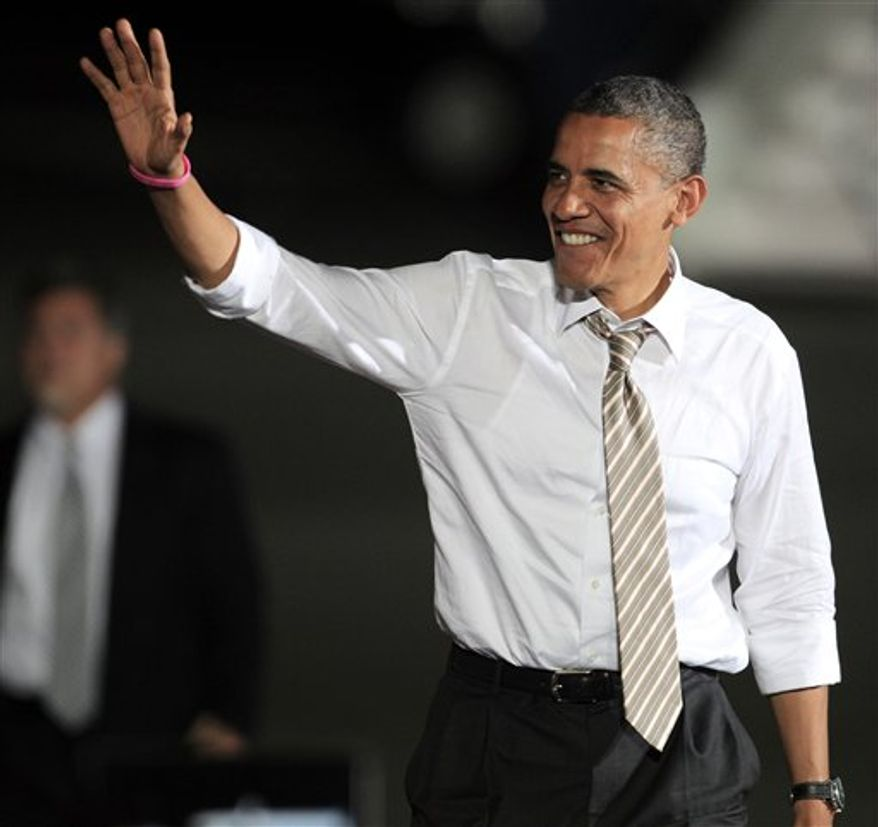President Barack Obama waves before he speaks at a campaign event at Burke Lakefront Airport Thursday, Oct. 25, 2012, in Cleveland. (AP Photo/Tony Dejak)