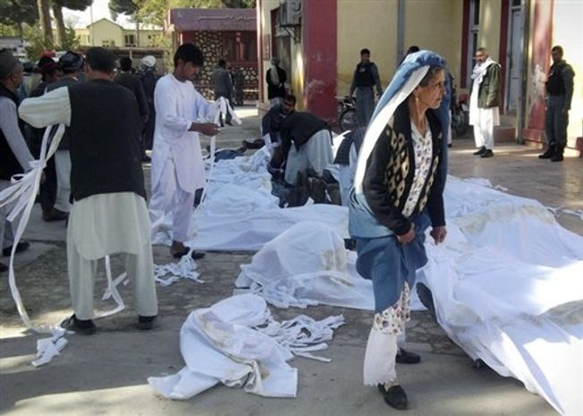 Bodies of suicide attack victims are covered in white cloth in the courtyard of a hospital in Maymana, Faryab province, northwest of Kabul, Afghanistan, Friday, Oct. 26, 2012. A suicide bomber blew himself up outside a mosque in northern Afghanistan