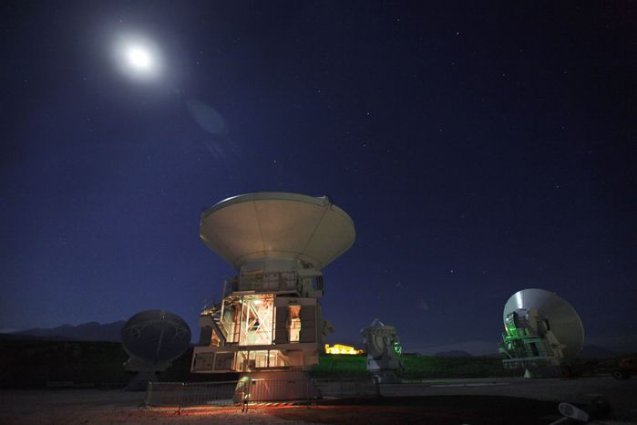 **FILE** The moon shines over radio antennas at the operations support facility of the Atacama Large Millimeter/submillimeter Array (ALMA) in the Atacama desert in northern Chile, one of the worlds largest astronomy projects, on Sept. 26, 2012. Linked as a single giant telescope, the radio antennas pick up wavelengths of li