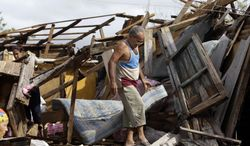 Resident Antonio Garces tries to recover his belongings Oct. 25, 2012, from his house in Aguacate, Cuba, which was destroyed by Hurricane Sandy. (Associated Press)
