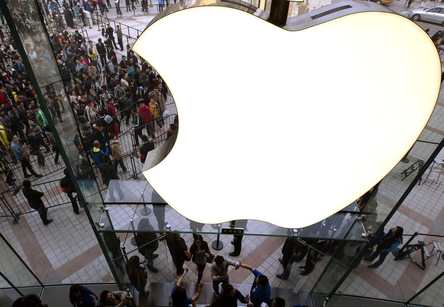 **FILE** Employees cheer customers as they enter a newly-opened Apple Store in Wangfujing shopping district in Beijing on Oct. 20, 2012. (Associated Press)
