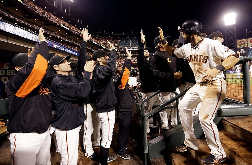 San Francisco Giants 2B Marco Scutaro is congratulated in the dugout after scoring on a sacrifice fly by RF Hunter Pence during the eighth inning of Game 2 of the World Series between the Giants and Detroit Tigers on Oct. 25, 2012, in San Francisco. (Associated Press)