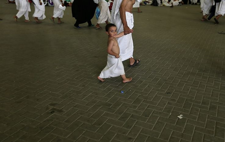"Youssef, 3, a Muslim pilgrim from Egypt, walks with his grandfather to cast stones at a pillar, symbolizing the stoning of Satan, in a ritual called ""Jamarat,"" the last rite of the annual hajj, in Mina near the Saudi holy city of  Mecca, Saudi Arabia, on Oct. 26, 2012. (Associated Press)"