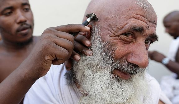 "A Muslim pilgrim has his head ritually shaved after he cast stones at a pillar, symbolizing the stoning of Satan, in a ritual called ""Jamarat,"" a rite of the annual hajj, the Islamic faith's most holy pilgrimage, in Mina near the Saudi holy city of Mecca, Saudi Arabia, on Oct. 26, 2012. The five-day rituals of Hajj began on Oct. 24 when millions arrived in the holy city. (Associated Press)"