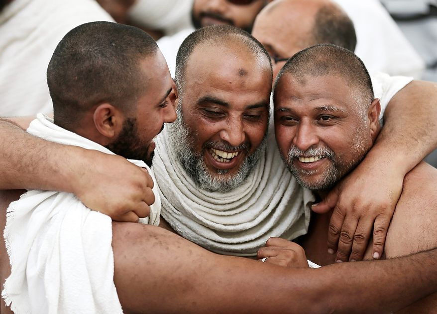 "Muslim pilgrims hug each other as they celebrate after casting stones at a pillar, symbolizing the stoning of Satan, in a ritual called ""Jamarat,"" a rite of the annual hajj, the Islamic faith's most holy pilgrimage, in Mina near the Saudi holy city of Mecca, Saudi Arabia, on Oct. 26, 2012. The five-day rituals of Hajj began on Oct. 24 when millions arrived in the holy city. (Associated Press)"