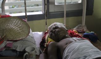 A Rakhine refugee lies on a bed Oct. 26, 2012, under medical treatment at Sittwe hospital in Sittwe, Rakhine State in western Myanmar. The death toll from recent ethnic violence in Myanmar's western state of Rakhine has surpassed 100, an official said Friday, as the government warned that the strife risks harming the country's reputation as it seeks to install democratic rule. (Associated Press)